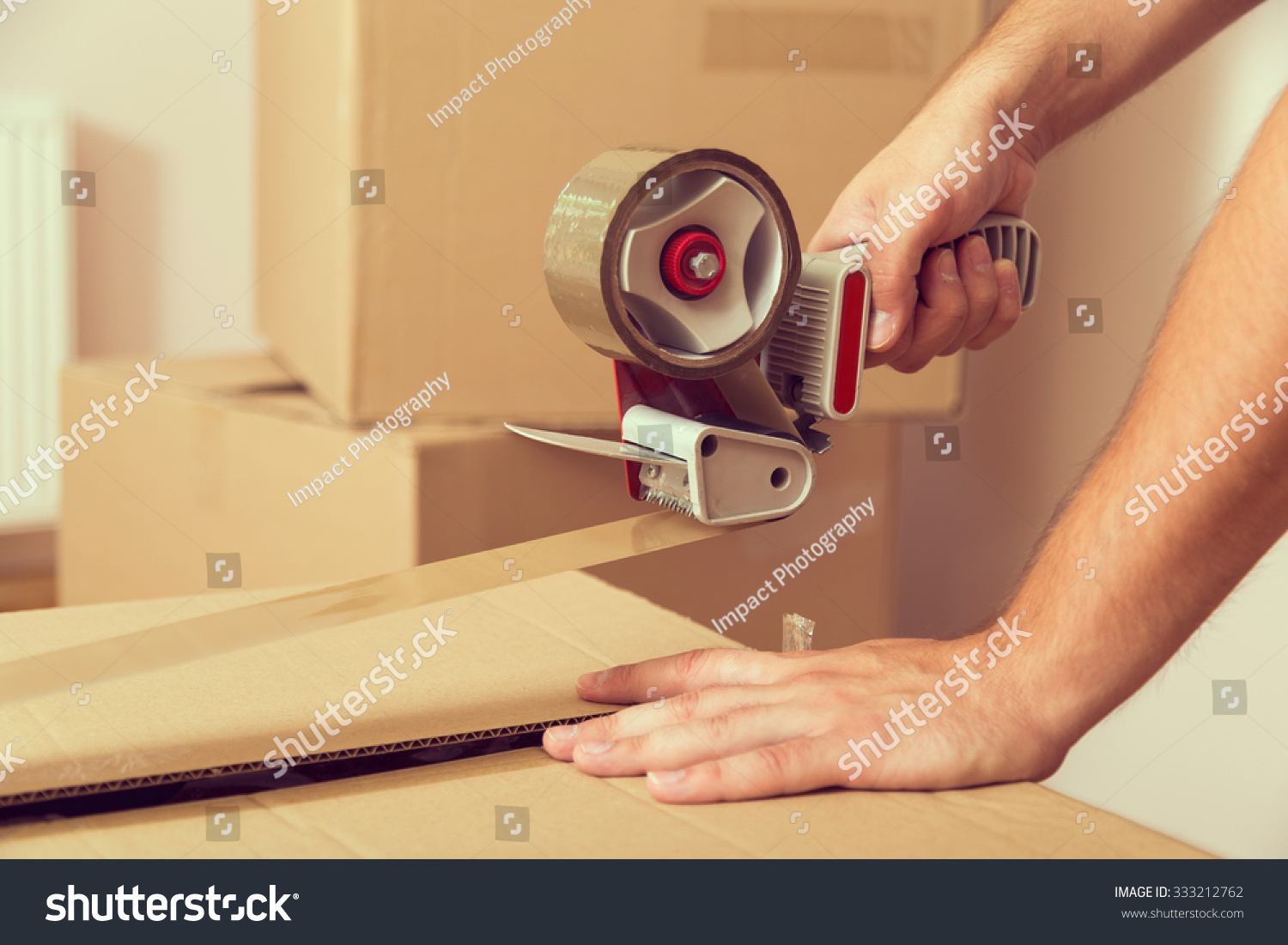 stock-photo-close-up-of-a-guy-s-hands-holding-packing-machine-and-sealing-cardboard-boxes-with-duct-tape-333212762